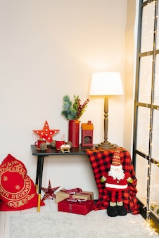 Christmas interior in the living room in red colors. on the table is a lamp, red mugs of cocoa, spruce branches in a vase. next to it is a bag of gifts and santa claus