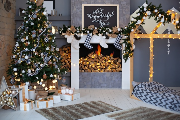 Christmas interior of living room with decorated christmas tree,  fireplace with christmas socks and wooden bed in shape of house. stylish interior of children's room, room decor in rustic style  loft