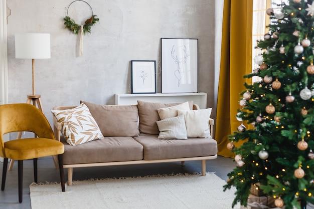 Новогодний интерьер, диван, венок из еловых веток, ёлка украшенная шарами и гирляндой, подготовка к новому году и рождеству