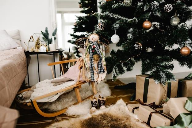 部屋にモミの木とクリスマスのインテリア。背景のクリスマスツリーに対して大きな弓を提示します。豪華な新年のギフトボックス。クリスマス休暇の構成。