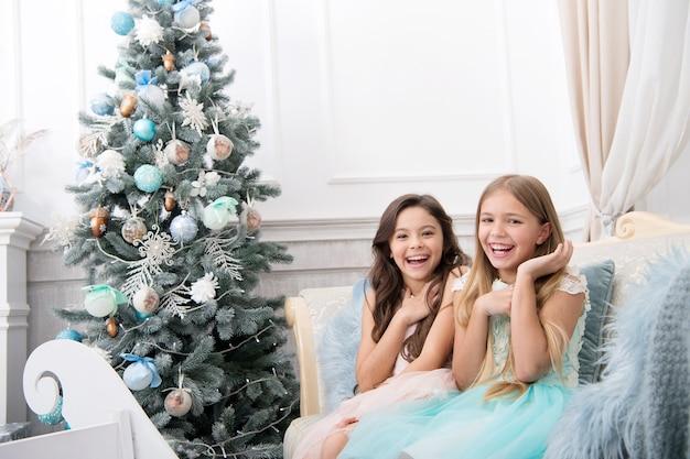 Рождественский интерьер. рождественские покупки в интернете. семейный отдых. с новым годом. зима. утро перед рождеством. девчонки. рождественская елка и подарки. ребенок наслаждается праздником.