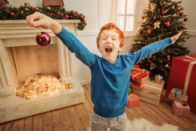 クリスマスが来ています。面白い縮れ毛の子供は、クリスマスのために家を飾っている間、彼の感情を中に入れて叫び続けることができません。