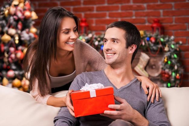 クリスマスは与える時間です。彼女のボーイフレンドに赤いギフトボックスを与え、バックグラウンドでクリスマスツリーと笑顔の美しい若い女性
