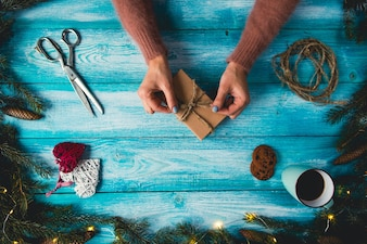 Christmas items on a blue wodden table. Woman's hands wrapping Christmas gift.