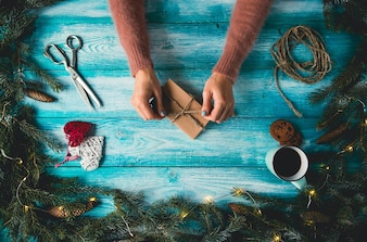 Christmas items on a blue wooden table. Woman's hands wrapping Christmas gift.