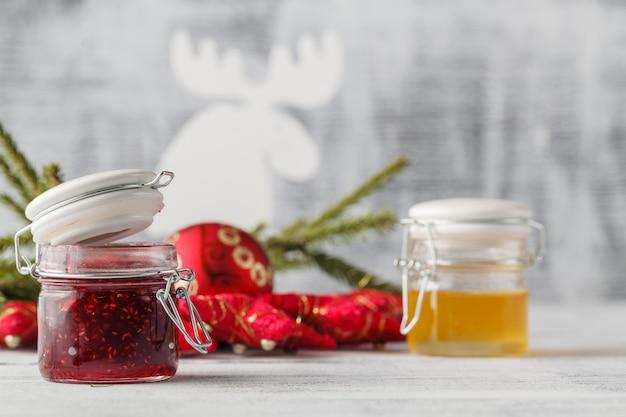 白い木製の選択と集中にお祝い装飾が施されたクリスマスジャム瓶。食用ギフト