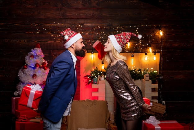 Christmas kiss couple in love christmas interior portrait of surprised and funny couple comic couple...