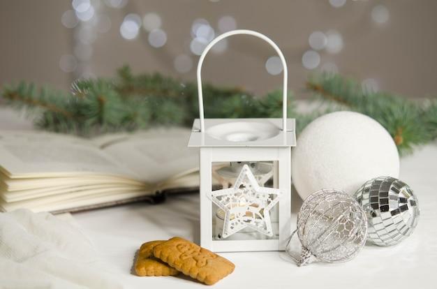 Рождественский фонарь, шары и печенье на фоне еловых веток. новогоднее украшение.