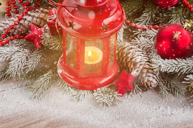 Рождественский фонарь крупным планом с вечнозеленым деревом и снегом