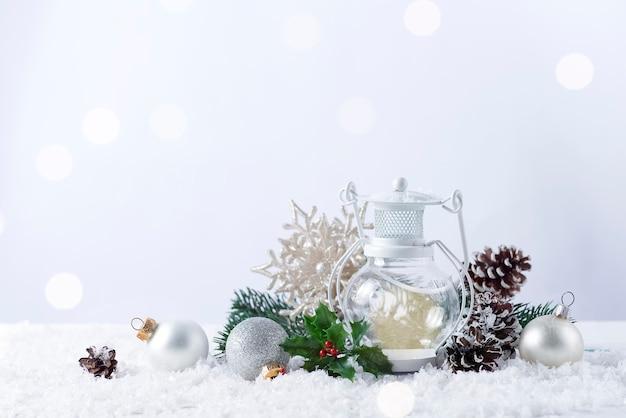 Рождественский фонарь на снегу с еловой веткой и зимним украшением на белом. концепция праздника рождества.