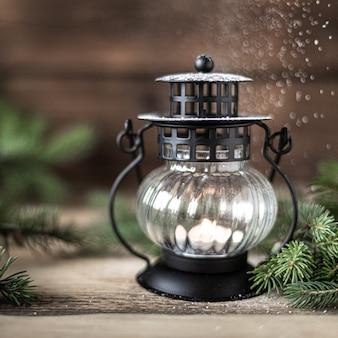 Рождественский фонарь со свечой и еловыми ветками с шишками на деревянном столе, копией пространства