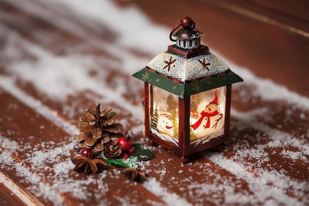 Рождественский фонарь со свечой на деревянном столе коричневого цвета