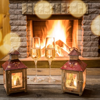 Christmas lanterns and champagne glasses near cozy fireplace, in country house.