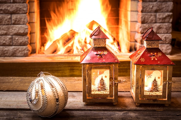 Christmas lanterns and christmas bauble near cozy fireplace, in country house.