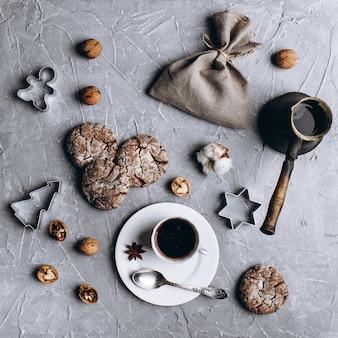 クリスマスのレイアウト。コーヒー、クッキー、ナッツ、綿、クッキーカッターを淹れるためのマグカップとレトロなポットのコーヒー