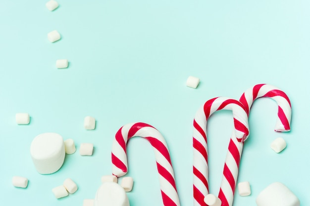 Christmas layout of frame of candy cane and marshmallows on a turquoise background with copy space