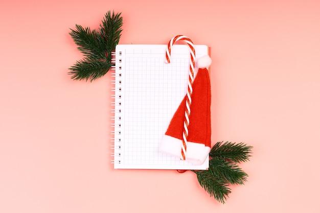 분홍색 배경에 크리스마스 장난감이 있는 메모용 크리스마스 레이아웃 노트북. 텍스트, 평면 스타일, 평면도를 위한 장소입니다.