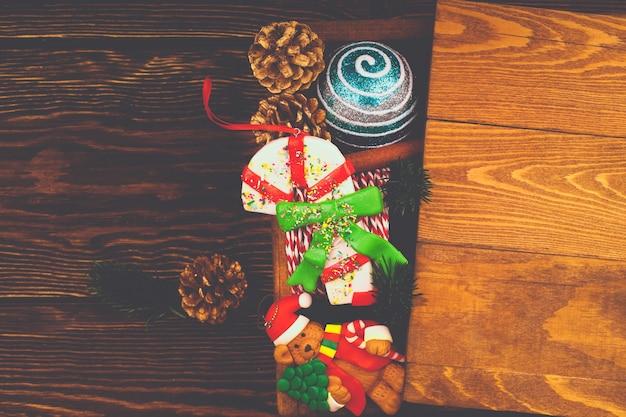 Рождественский макет на деревянном фоне. винтажная деревянная коробка с елочными игрушками. вид сверху, плоский стиль.