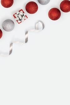 빛나는 빨간색과 은색 크리스마스 공과 작은 선물 상자 또는 흰색 선물이 있는 크리스마스 레이아웃