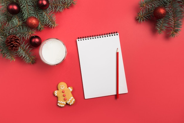 Christmas letter for santa claus with milk, cookies, gingerbread on red. top view and space for your text. flat lay.