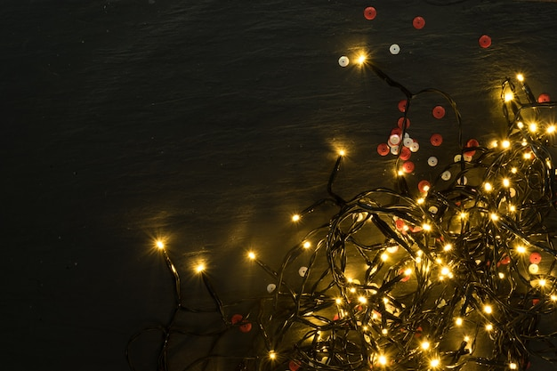 Christmas light on wooden background top view with copyspace