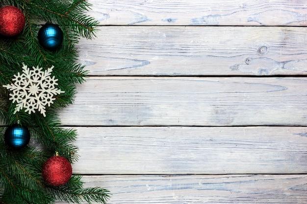 モミの枝とクリスマスライト木製の背景クリスマスボールと新年のおもちゃ
