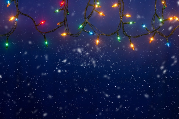 Christmas lights on blue background with copy space