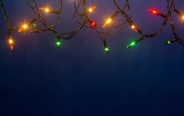 Christmas lights on blue background with copyspace
