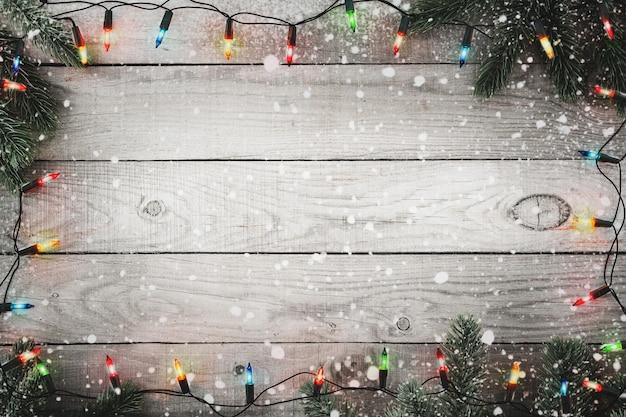 Рождественские огни лампочки и еловая ветка и снежинка на деревенском деревянном столе