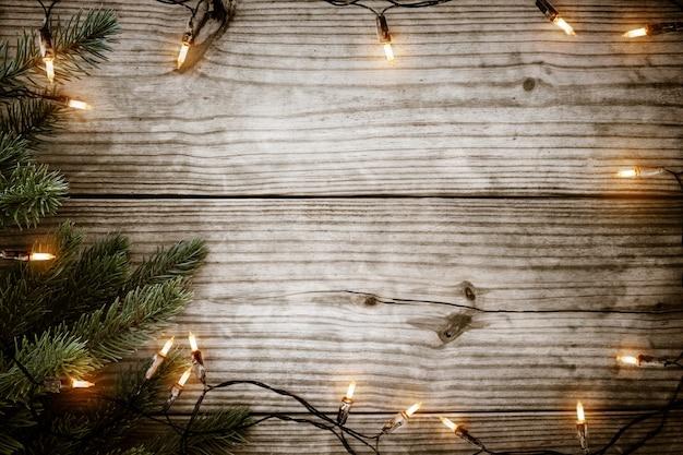 Рождественские огни лампочки и еловая ветка на деревенском деревянном столе
