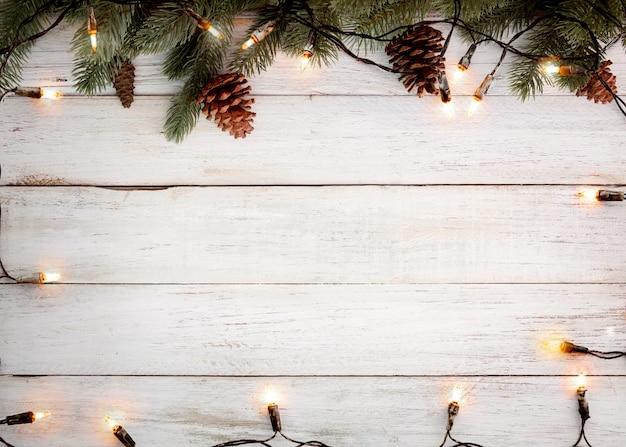 Рождественские огни лампы и украшения из сосновых листьев на белой деревянной доске