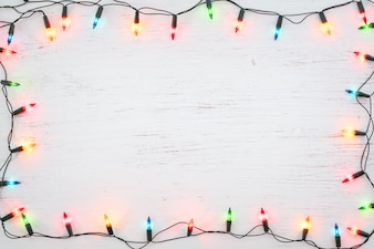 Christmas lights bulb frame decoration on white wood. Merry Christmas and New Year holiday