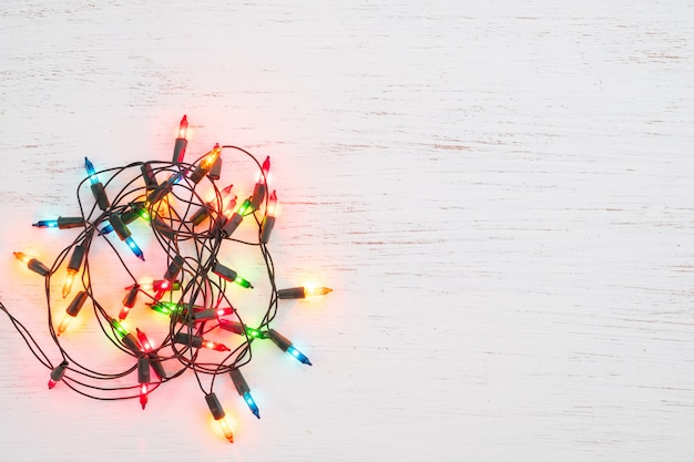Christmas lights bulb on white wood. merry christmas and new year holiday background. top