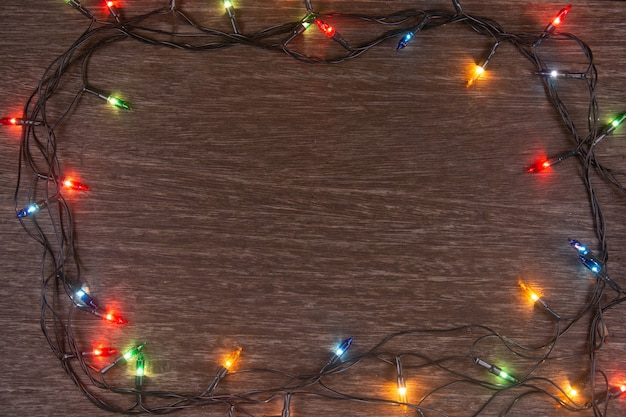 Christmas lights on dark wooden background merry christmas and happy new year with copy space f