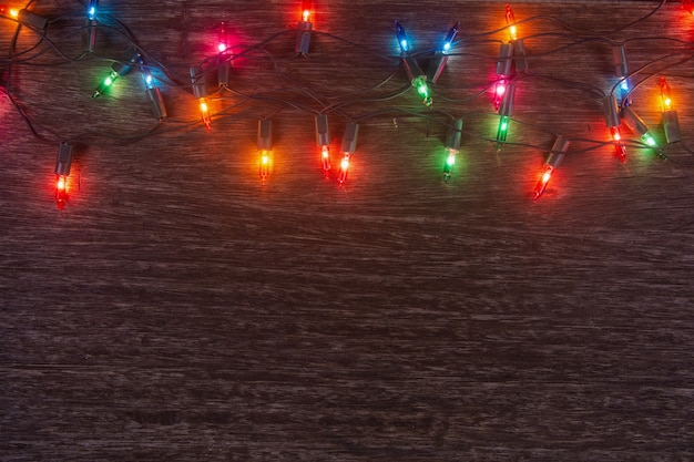 Christmas lights on dark wooden background merry christmas and happy new year with copy space