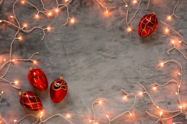 Christmas lights frame on dark stone background with red ornaments