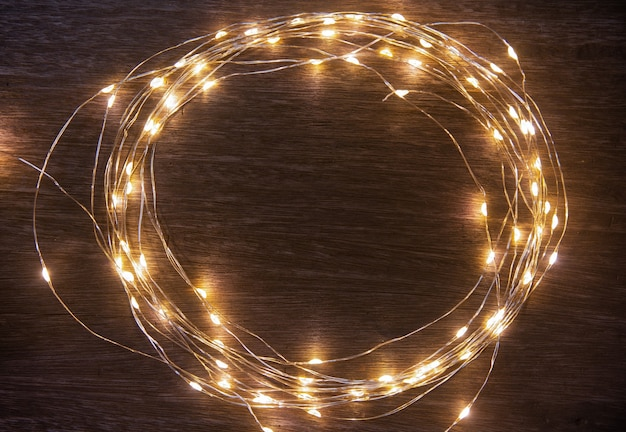 Christmas lights frame decoration on dark wood with copy space merry christmas and newyear