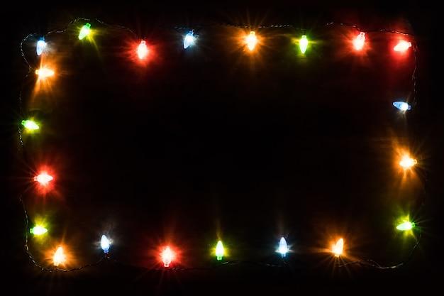 クリスマスライトフレーム。新年の背景。クリスマスの背景木製の背景に色付きのライトとランプが付いたクリスマスの花輪。テキスト用の空き容量。コピースペースで表示