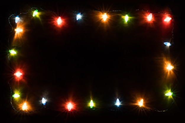 Christmas lights frame. new year's background. christmas background christmas garland with colored lights and lamps on a wooden background. free space for text. view with copy space