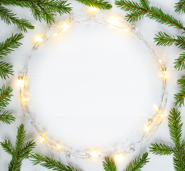 Christmas lights garland circular border and fir branches with copy space.