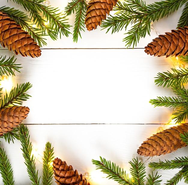 クリスマスライトガーランドの円形の境界線、トウヒの円錐形、コピースペースのあるモミの枝。
