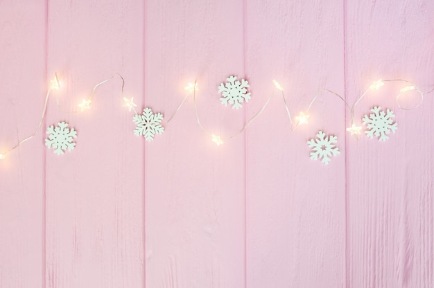 Christmas lights garland with snowflakes border over pink wooden