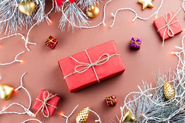 Рождественские огни, подарочная коробка, подарки, золотые украшения и еловые ветки на коричневом фоне