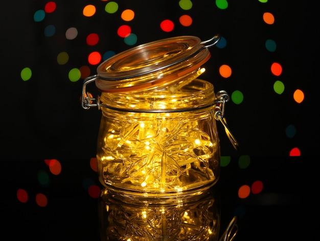 Christmas lights in glass bottle on blur lights background