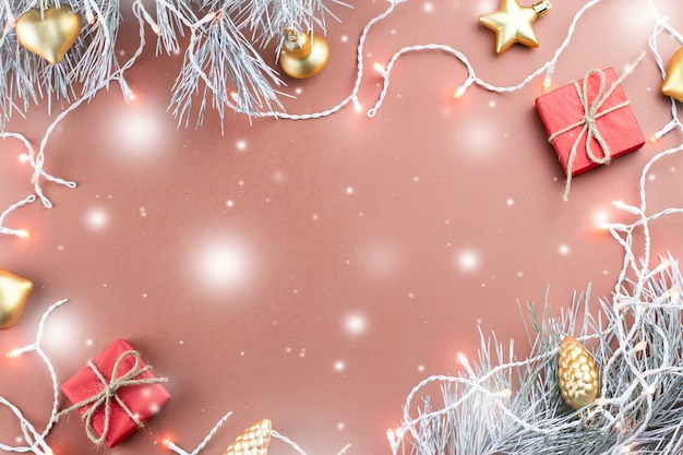 Christmas lights, golden ornaments, red giftbox and fir branches on brown background