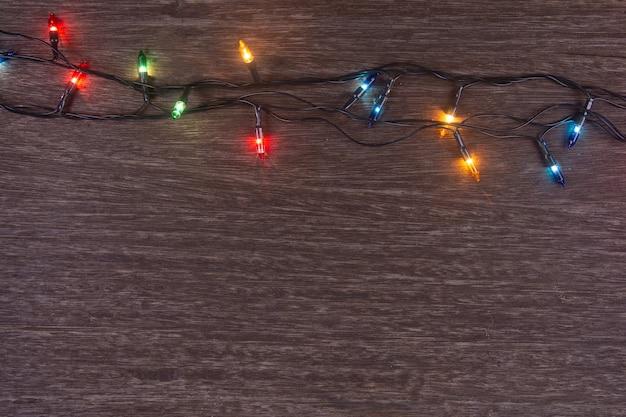 어두운 나무 배경에 크리스마스 조명 메리 크리스마스와 복사 공간이 있는 새해 복 많이 받으세요
