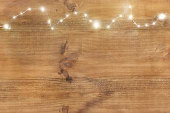 Christmas lights on top on wooden background.