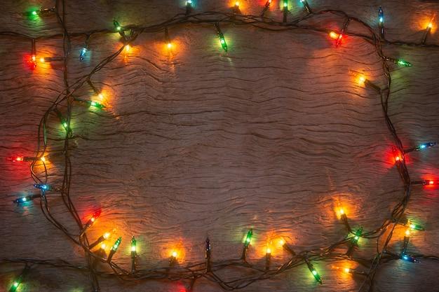 木の板の背景にクリスマスライトメリークリスマスとコピースペースで新年あけましておめでとうございます