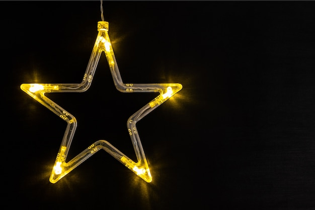 Christmas lights in the shape of a star on a background of dark chalk board.