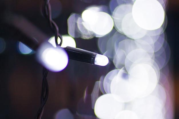 ボケ味のクリスマスライト。新年のウィンドウでガーランドのクローズアップ